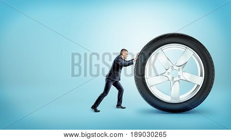 A small businessman pushing up at a huge new car tire on blue background. Car expenses. Spare parts delivery. Tire replacement.