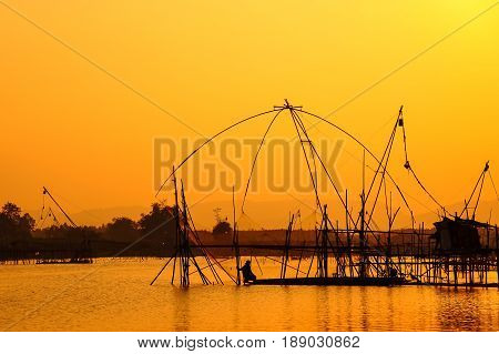Traditional fishing tools and fishing boat in swamp during sunset