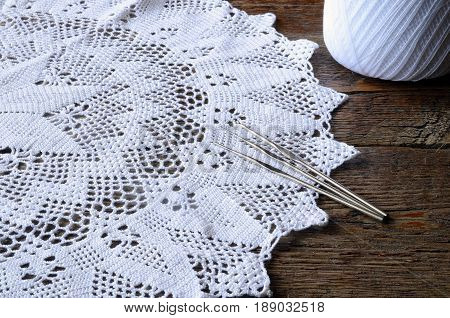A close up image of a white crochet doily and three metal crochet hooks.