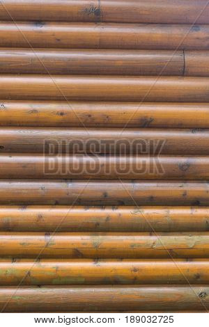 smooth round logs of a modern log home provide a woodsy background