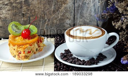 Cappuccino coffee and fruits cake. A cup of latte, cappuccino or espresso coffee with milk put on a wood table with dark roasting coffee beans. Drawing the foam milk on top.