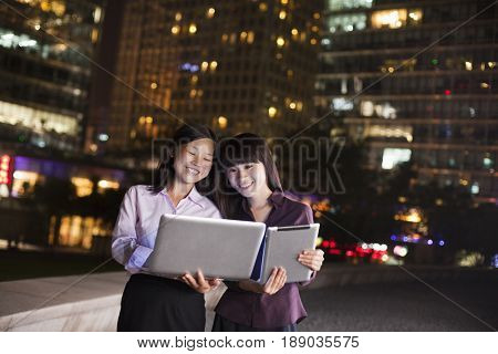 Chinese business women using digital tablet and laptop