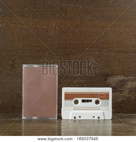 White and brown retro audio cassette and case on the wooden shelf