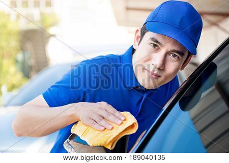 Auto service staff polishing (cleaning) car with microfiber cloth car detailing or valeting concept