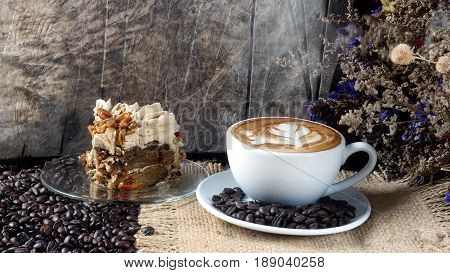 Cappuccino coffee and cake. A cup of latte, cappuccino or espresso coffee with milk put on a wood table with dark roasting coffee beans. Drawing the foam milk on top.
