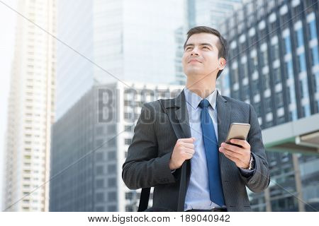 Young businessman using mobile phone while carrying bag in the city - business travel and roaming concepts