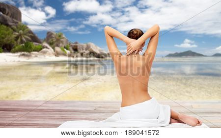 beauty, people and bodycare concept - beautiful young woman in white towel with bare top over exotic beach background