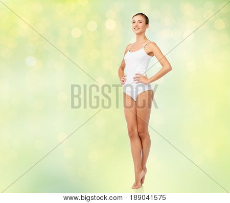 beauty, people and bodycare concept - beautiful young woman in white underwear over summer green lights background
