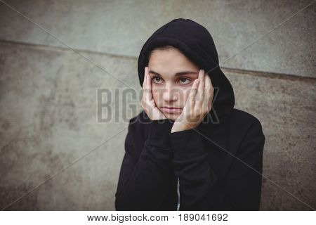 Anxious teenage girl in black hooded jacket standing with hand on face at school