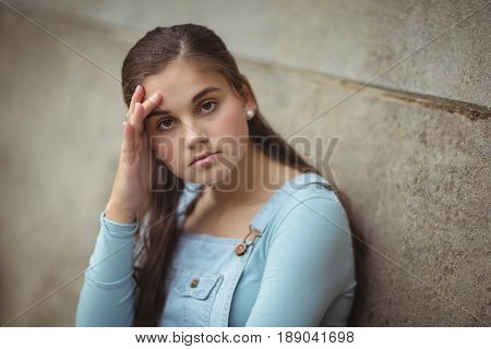 Portrait of anxious teenage girl leaning on wall at school
