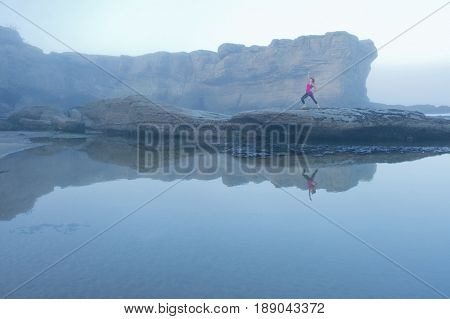 Caucasian woman practicing yoga on rock formations