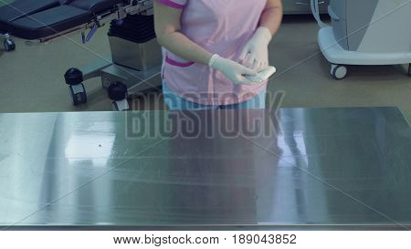 Surgical assistants sterilizing a table in operation room