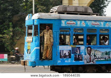 CALCUTTA INDIA - 06 DECEMBER 2009: Conductor standing on stairs of the municipal tram in Calcutta