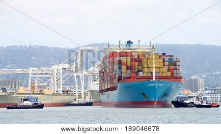 Oakland CA - May 30 2017: Multiple tugboats work together to push and pull cargo ship GERDA MAERSK turning it 180 degrees prior to docking at the Port of Oakland.