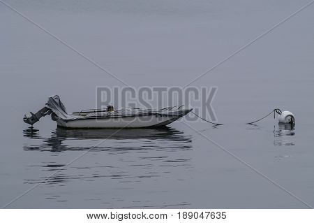 Small skiff at its moorings on a foggy morning.