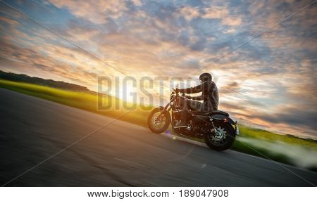 Dark motor-biker riding high power motorbike in nature with beautiful sunset light. Travel and transportation. Freedom of motorbike riding