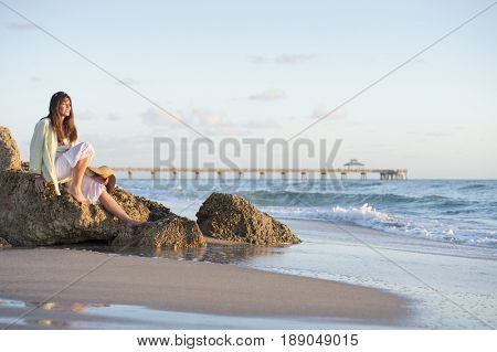 Caucasian woman sitting on beach