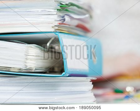 Stack of many binders with documents reports and paperwork. Office objects concept.