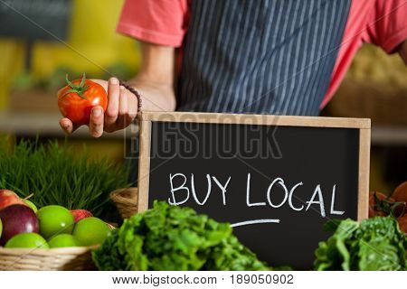 Mid section of male staff holding fresh tomatoes with slate board in organic section of supermarket