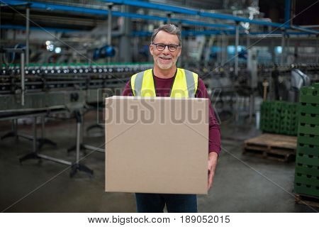 Portrait of factory worker holding cardboard box in drinks production factory
