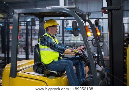 Factory worker driving forklift in drinks production factory