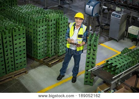 Male factory worker maintaining record on clipboard in drinks production factory