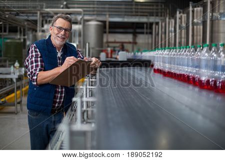 Portrait of male factory worker maintaining record on clipboard in drinks production factory poster