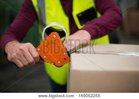 Close-up of factory worker sealing cardboard boxes in drinks production factory