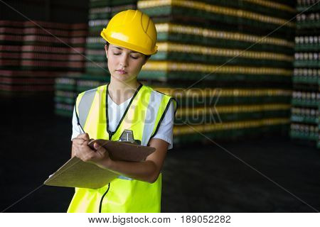 Attentive female factory worker writing on clipboard in factory