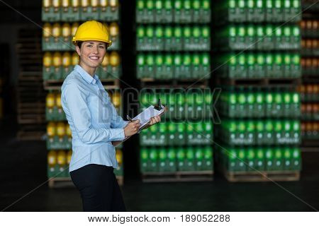 Portrait of female factory worker maintaining record on clipboard in factory