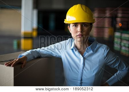 Portrait of female factory worker standing with hand on hip in factory