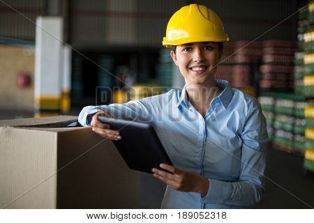 Portrait of female factory worker standing with digital tablet in factory
