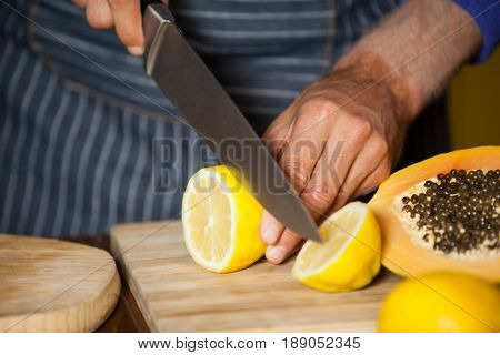 Mid-section of male staff cutting lemon in organic section of supermarket