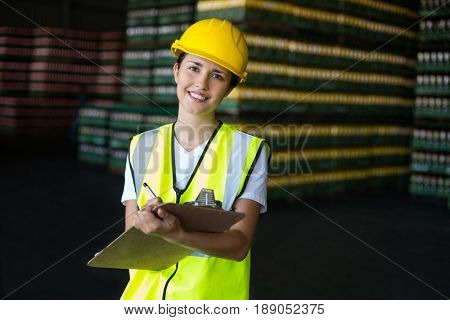 Portrait of smiling female factory worker writing on clipboard in factory