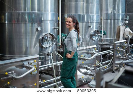 Female factory worker standing near control wheel of storage tank at drinks production factory