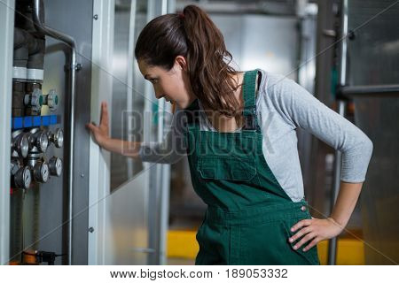 Female factory worker inspecting machinery at drinks production factory