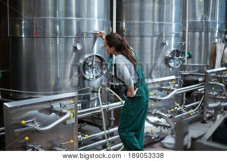 Female factory worker looking at control wheel of storage tank at drinks production factory