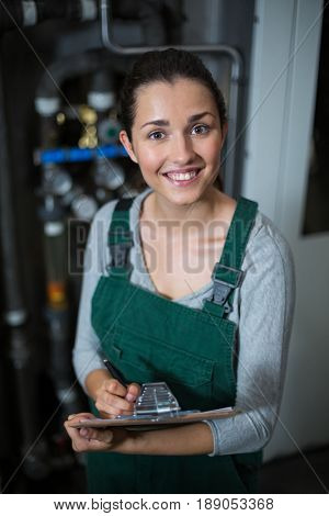 Portrait of female factory worker maintaining record on clipboard in drinks production factory