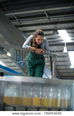 Female factory worker inspecting production line at drinks production factory