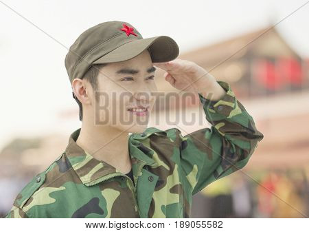 Chinese soldier in uniform saluting