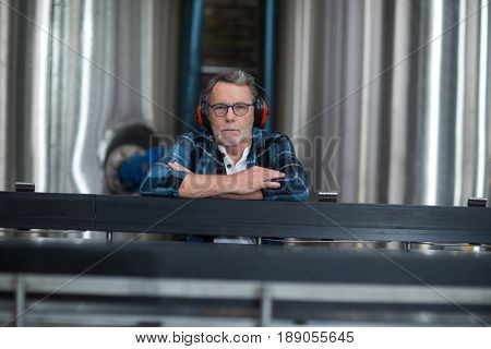 Portrait of male factory worker sitting at drinks production factory