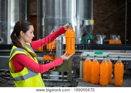 Female factory worker examining a bottle of juice in factory