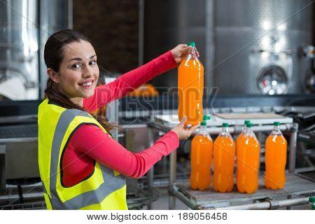 Portrait of female factory worker holding a bottle of juice in factory