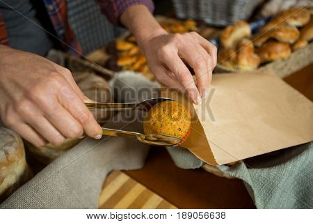 Mid section of staff packing cup cake in paper bag at counter in bakery shop