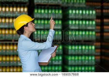 Attentive female factory worker maintaining record on clipboard in factory