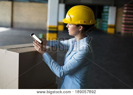 Female factory worker using mobile phone in factory