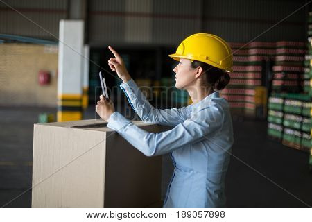 Attentive female factory worker maintaining record on mobile phone in factory
