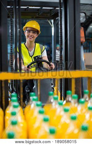 Portrait of female factory worker loading packed juice bottles on forklift in factory
