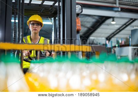 Attentive female factory worker driving forklift in factory