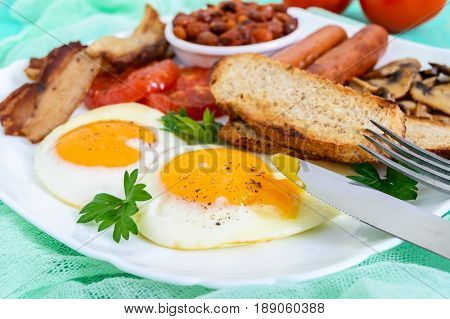 Traditional English breakfast: bacon mushrooms eggs tomatoes sausages beans toast on a white plate on a bright wooden background. England classic cuisine. Close up